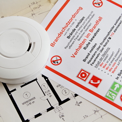 Feuermelder auf Brandschutzordnung und Lageplan eines Gebäudes
