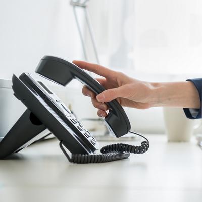 Hand am Telefonhörer neben dem Telefon